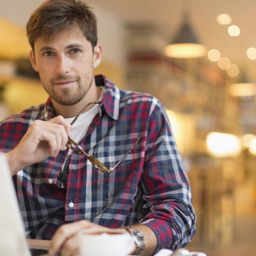Portrait confident man working at laptop in cafe